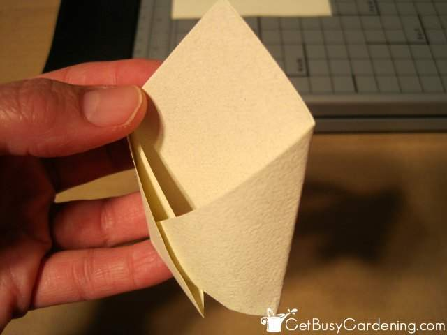 Tucking in the side flaps to secure the paper envelope