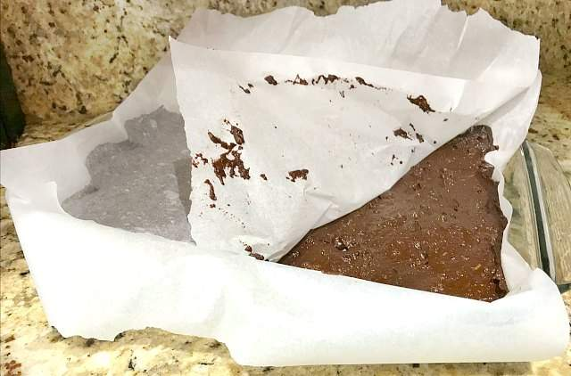 Using parchment paper to press zucchini brownie batter into the baking dish