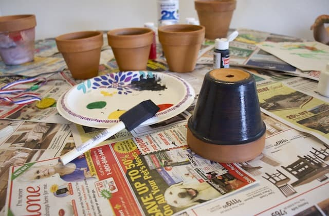 Terracotta pot painted with the first layer of paint