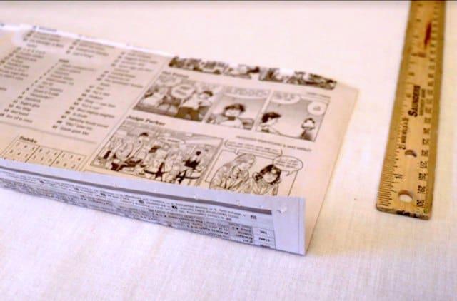 Creasing the strip of newspaper