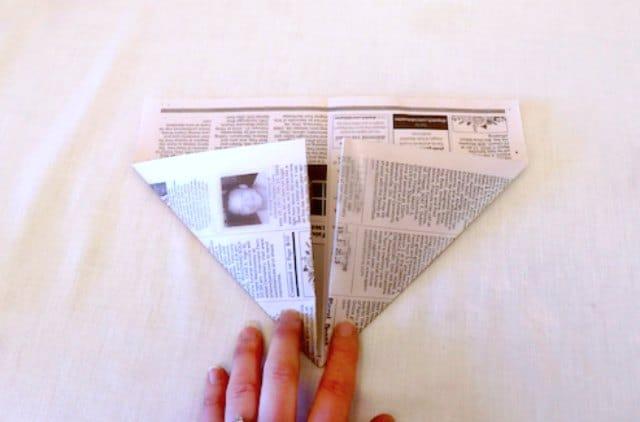 Folding the bottom corners of the newspaper