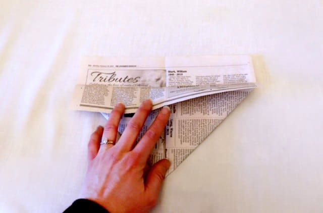 Folding the top edge of the newspaper over the triangles