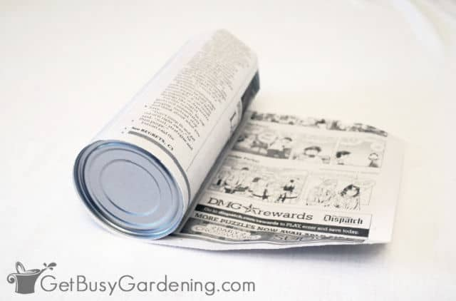 Rolling the newspaper around an aluminum can